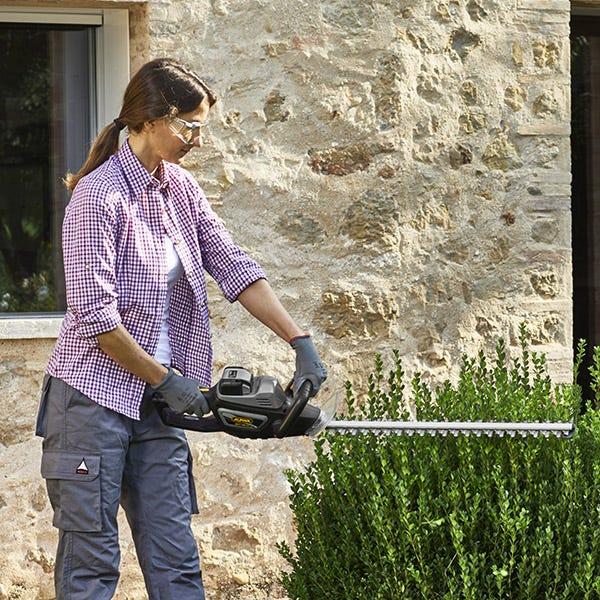 Kvinna klipper häck med Alpina 40 V batteridrivna häcksax