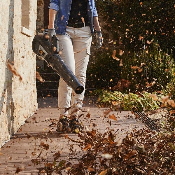 Kvinna använder Alpina 40 V batterilövblås för att rengöra gångväg